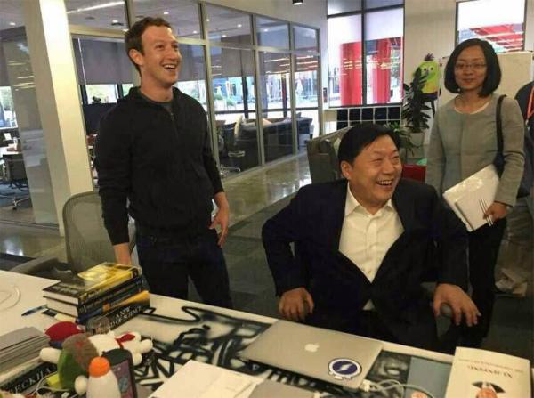 Lu Wei achter het bureau van Mark Zuckerberg, met links de Xiami mascotte en rechts de verzamelde speeches van Xi Jinping.